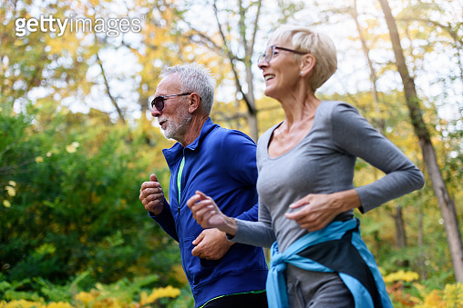 Cheerful active senior couple jogging in the park in the morning