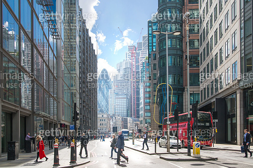 City of London busy street with view at the Gherkin building at the background, lots of people crossing the road, cars and buses