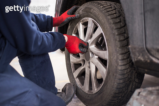 Tire repairman unscrewing the bolts on the rim of car wheel with
