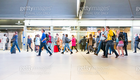 Office workers walking through Canary Wharf tube station in early morning, on the way to work.  Rush hours