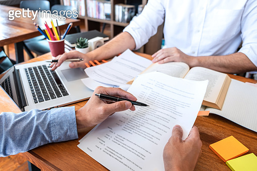 Teaching helping and study course, Team of young teacher or tutor helps students to learning in classroom for homework a test or exam at desk with papers
