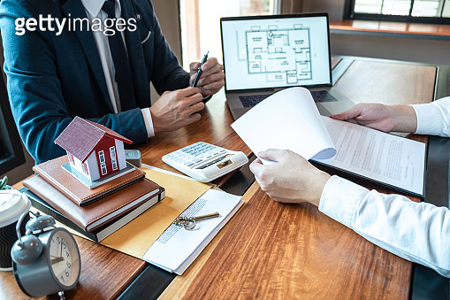 Sale purchase contract to buy a house, Real estate agent are presenting home loan and giving keys to customer after signing contract to buy house with approved property application form