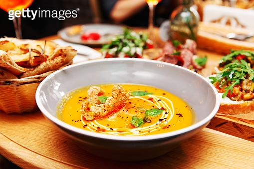 Deep plate with pumpkin soup, Italian restaurant, toned
