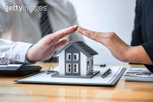 Real estate agent and customer covering Small house model and protection by hands