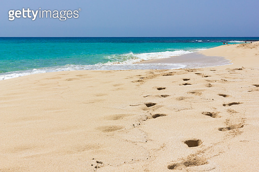 Footsteps along seashore on empty beach with pristine water