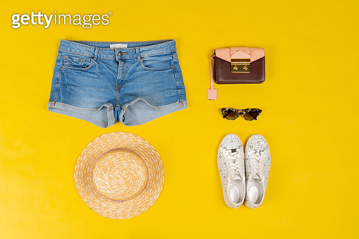 Set of female clothes and accessories on bright yellow background