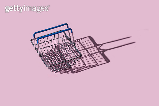 Empty metal shopping basket on a pastel pink background with copy space. Top view