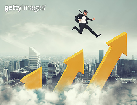 Businessman jumps on increasing statistic arrows to reach the top