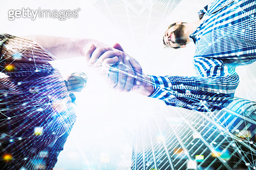 Handshaking business person in casual wear. concept of teamwork and partnership. double exposure