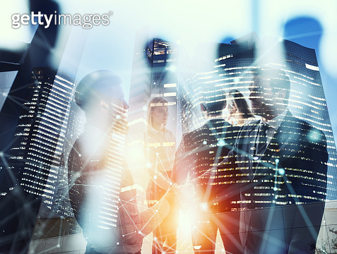 Businessmen that work together in office at night. Concept of teamwork and partnership. double exposure