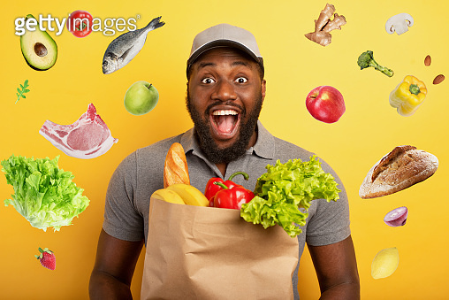 Deliveryman with happy expression ready to deliver bag with food. Yellow background