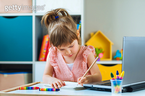 Beautiful little girl writing homework using notebook for distance learning