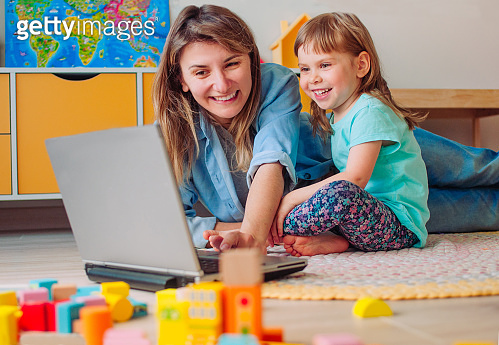 Smiling mother and toddler daughter looking at the notebook