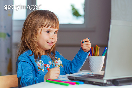 Happy little four years old girl doing homework using the notebook for distance learning