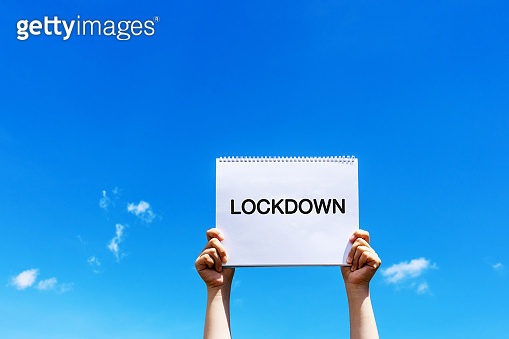 Hands holding paper note with Lock down text