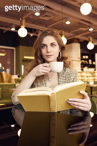 young beautiful woman drinks coffee and reading book