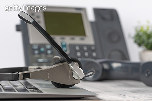 VOIP headset headphones telephone on laptop on office desk concept for communication, it support, call center and customer service help desk. Business center background, phone support service calls.