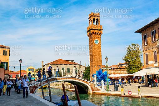 Murano, Italy - September, 2017: Murano, Venice, Italy in the summer season. Bridge with canal and Murano campanile