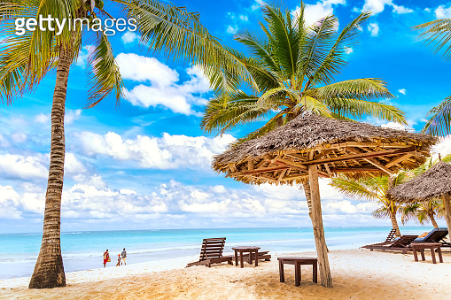 Sun loungers under umbrella and palms on the sandy beach by the ocean and cloudy sky. Vacation background. Idyllic beach landscape in Diani beach, Kenya, Africa