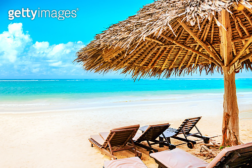 A sun lounger under an umbrella on the sandy beach by the ocean and cloudy sky. Vacation background. Idyllic beach landscape in Diani beach, Kenya, Africa