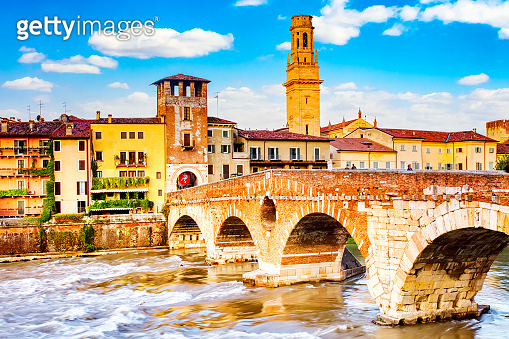Famous Verona landmark. Ponte di Pietra over Adige river during sumer sunny day in Verona, Italy