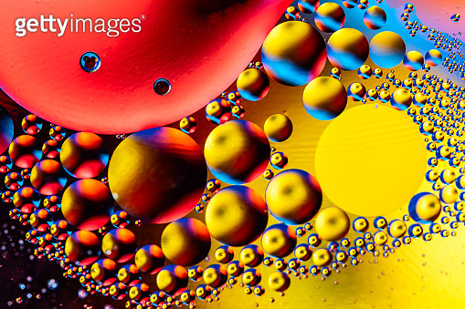 Macro shot of oil bubbles with water on colorful background. Space and universe planets styled psychedelic abstract image