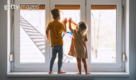 Little children on background of painting rainbow on window. Photo of kids leisure at home.