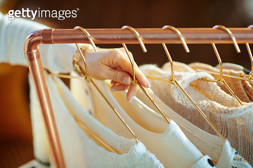 Closeup on trendy woman taking sweaters on hanger from rack