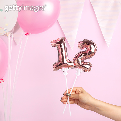 Decoration for birthday party. Female hand holding golden balloon in form of 12 number on pink background.