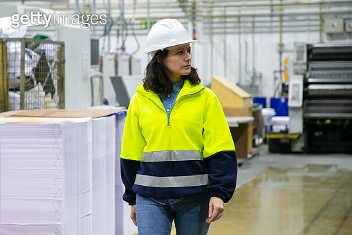 Serious female industrial professional watching production