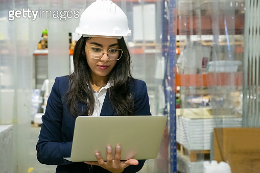 Focused female plant manager using laptop computer onsite