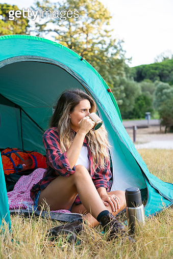 Caucasian young woman drinking tea, sitting in tent
