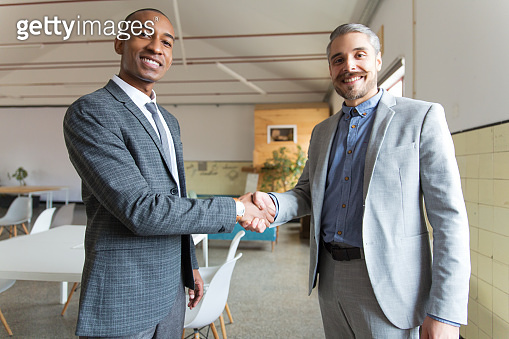 Two smiling businessmen shaking hands and looking at camera