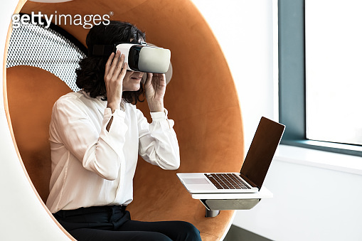 Business woman watching virtual presentation with VR goggles
