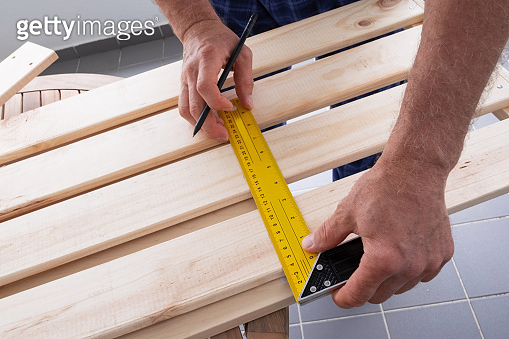 Carpenter measuring distance with construction ruler