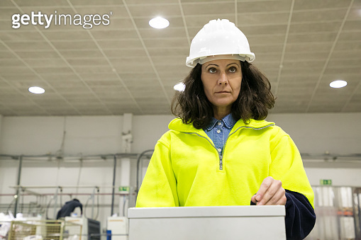 Focused factory worker operating production process