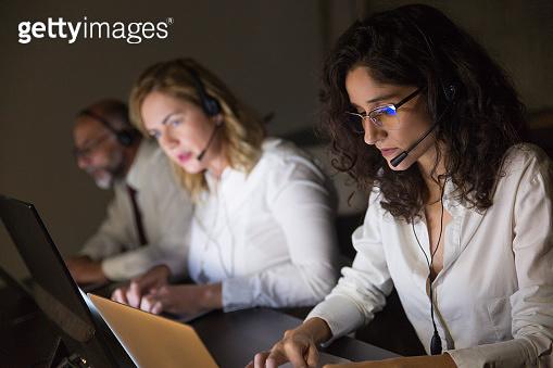 Focused teleworkers working in dark office