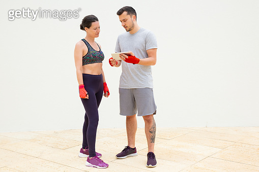 Attractive trainer explaining training plan on tablet