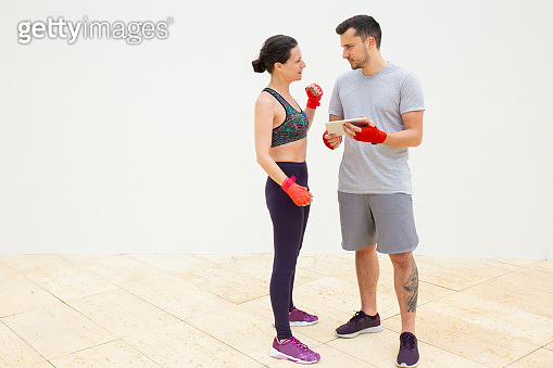 Man and woman discussing training plan with hand wrapped