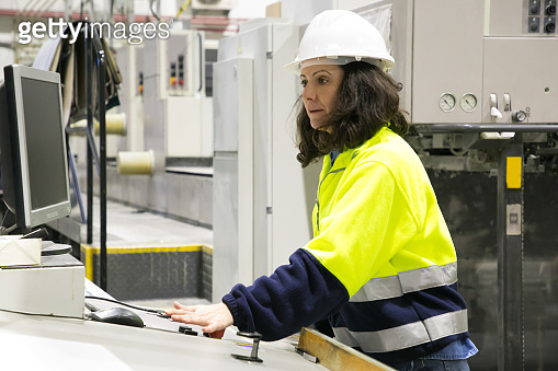 Serious female machine operator at her workplace