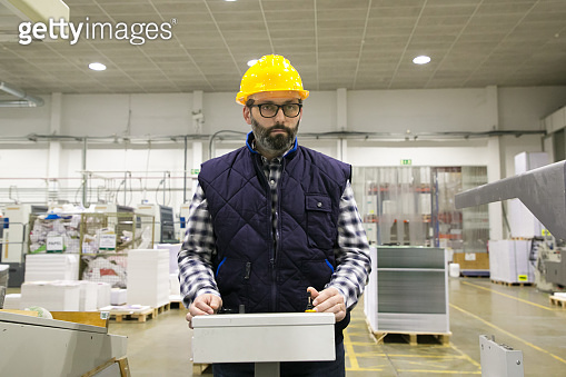 Serious factory machine operator pressing buttons