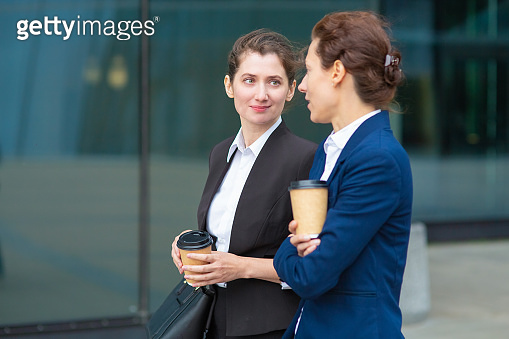 Positive office female friends with takeaway coffee cups
