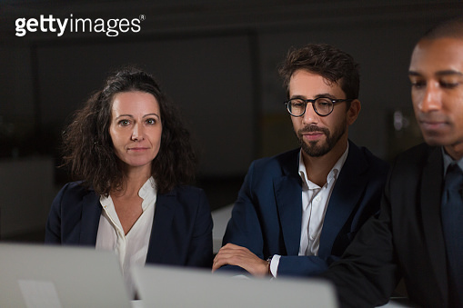 Business colleagues using laptops in dark office