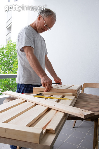 Handyman adjusting wooden shelves to each other