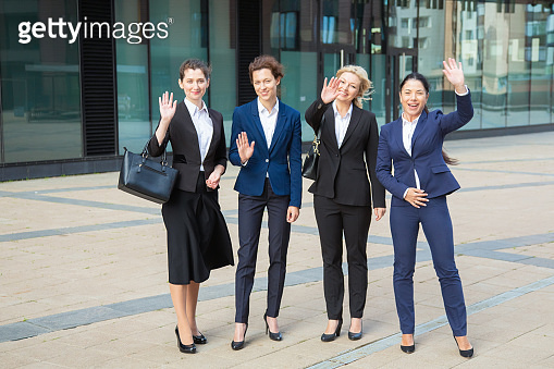 Cheerful business ladies team standing together near office
