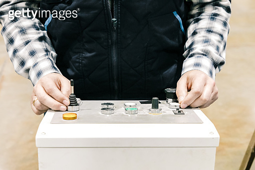 Cropped shot of factory machine operator pressing buttons