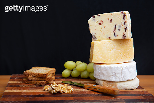 Stack of whole and cut cheeses and snacks