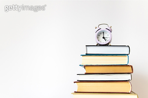 Purple small alarm clock on stack of books on white background wall with copy space. Concept of time to study, read books. Concept of preparing for exams