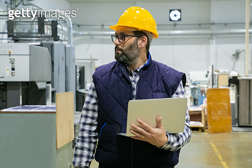 Serious male industrial worker using laptop computer onsite