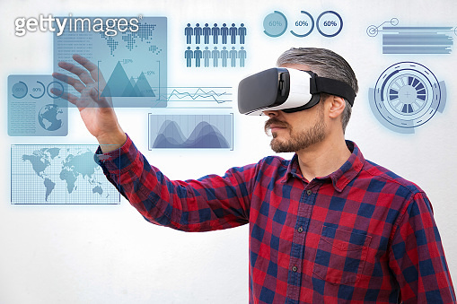 Concentrated man in VR headset touching virtual data analysis
